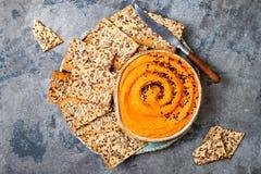 Hummus della zucca esperto con olio d'oliva e semi di sesamo neri con gli interi cracker del grano Aperitivo o spuntino vegetaria Immagine Stock