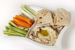 Hummus dip and crudites. A dip tray with hummus, bread, carrot sticks, celery and cucumber Stock Images