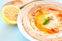 Hummus dip plate and lemon on wooden table Stock Image