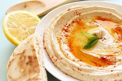 Hummus dip plate and lemon on wooden table Stock Photography