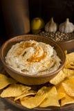 Hummus in an earthenware dish and garlic Stock Image