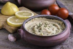 Hummus in eigengemaakte komcitroen en tomaten op rustiek bureau stock foto's