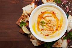 Hummus eller houmous, aptitretare som göras av mosade kikärtar, tahini, citron, vitlök, olivolja, persilja och paprika Arkivbild
