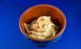 Hummus en cuenco tradicional con el fondo azul Imagen de archivo