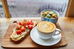 Hummus en tomatensandwich, salade en verse hete cappuccinokoffie Stock Fotografie
