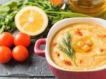 Hummus fresco in una ciotola porpora, in pomodori, in limone ed in un mazzo di pianta su una tavola rustica fotografie stock