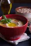 Hummus hecho en casa con albahaca, ajo y aceite de oliva imagenes de archivo