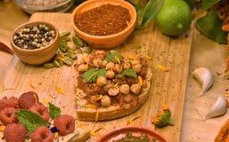 Hummus, Himbeeren und essbare Blumen auf Toast lizenzfreies stockbild