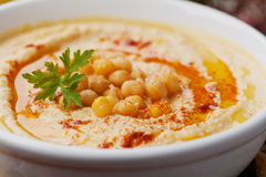 Hummus or houmous, appetizer made of mashed chickpeas, tahini, lemon, garlic, olive oil, parsley and paprika Stock Photos