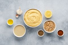 Hummus ingredients. Chickpea, tahini, olive oil, sesame, herbs. Hummus ingredients. Chickpea, tahini, olive oil, sesame and herbs on gray background. Set of raw stock photography
