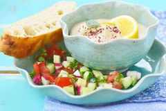 Hummus. With lemon and vegetable salad in to blue bowl stock photos