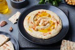Hummus, mergulho do grão-de-bico, com especiarias e pão árabe, flatbreadin uma placa preta no fundo de pedra cinzento Fotos de Stock