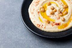 Hummus, mergulho do grão-de-bico, com especiarias e pão árabe, pão liso em uma placa preta Copie o espaço Fotografia de Stock Royalty Free