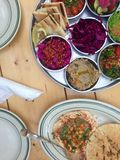 Hummus and Middle Eastern salads on a restaurant table. A top-down view of a wooden table. On one plate, pita bread sits next to hummus topped with chickpeas royalty free stock photo