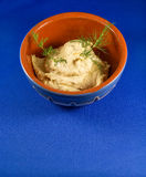 Hummus na bacia tradicional com fundo azul Foto de Stock Royalty Free