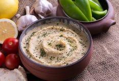 Hummus in naar huis bewerkte kom met knoflook en tomaten stock foto's