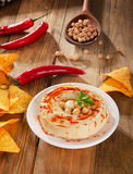 Hummus with nachos and chilli peppers Stock Photography
