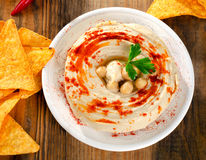 Hummus with nachos on  a wooden table. Royalty Free Stock Images