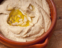 Hummus, olive oil and pine nuts Royalty Free Stock Photography