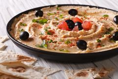 Hummus with olives and herbs on a plate close-up. horizontal Stock Image