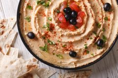 Hummus with olives and tomatoes horizontal top view Royalty Free Stock Photos