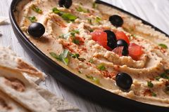 Hummus with olives and tomatoes on a plate close-up. Stock Image
