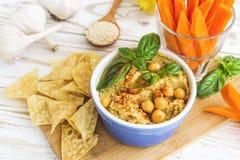 Hummus orgânico caseiro fresco com cheaps e manjericão do pão árabe Fotos de Stock Royalty Free