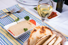 Hummus Paired with White Wine. And pia breads and served on a blue striped cotton placement Stock Photos