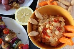 hummus Pflanzenkost, gesunde Nahrung auf schwarzer Tabelle mit Gemüse lizenzfreie stockfotos