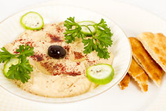 Hummus with Pita. Hummus garnished with cucumbers and parsley and side of pita bread Stock Images