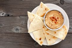 Hummus with pita bread on a plate, above view over wood Royalty Free Stock Photo