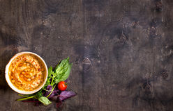 Hummus on a plate with cherry tomatoes and herbs on a dark woode Stock Images