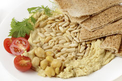 Hummus with roasted pine nuts. Hummus and lightly roasted pine-nuts dip, garnished with cherry tomatoes and young salad leaves, viewed close-up royalty free stock photos