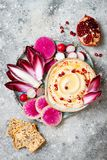 Hummus seasoned with olive oil and paprika and fresh vegetables: radishes, watermelon radish, red chicory, pomegranate. Homemade hummus seasoned with olive oil Royalty Free Stock Photos