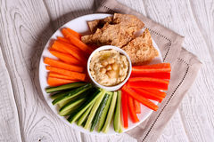 hummus served in a bowl with fresh vegetable sticks Royalty Free Stock Photo