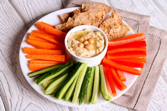 Hummus served in a bowl with fresh vegetable sticks Royalty Free Stock Image