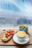 Hummus and tomato sandwich, salad and fresh hot cappuccino coffee Royalty Free Stock Photos
