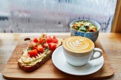 Hummus and tomato sandwich, salad and fresh hot cappuccino coffee Stock Image