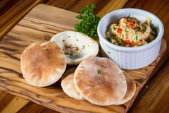 Hummus topped with paprika. Ramekin filled with hummus topped with paprika and parsley as a garnish served with small pita bread rounds served on a wooden board royalty free stock photos