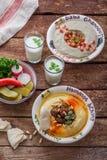 Hummus in traditioneller der Libanon-Platte auf einer rustikalen Tabelle mit Gemüse lizenzfreie stockbilder