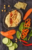 Hummus tradizionale casalingo con le verdure, cracker sul nero Fotografia Stock