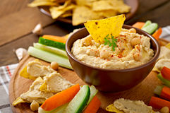 Hummus with vegetables, olive oil and pita chips Royalty Free Stock Images