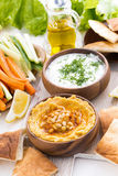 Hummus in wooden bowl with pita bread and fresh vegetables Stock Image