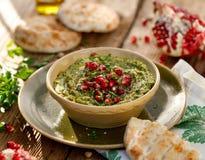 hummus Ziołowy hummus z dodatkiem granatowów ziaren, pietruszki, oliwa z oliwek i aromatycznych pikantność w ceramicznym garnku n zdjęcie stock