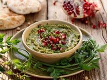 hummus Ziołowy hummus z dodatkiem granatowów ziaren, pietruszki, oliwa z oliwek i aromatycznych pikantność w ceramicznym garnku n obraz stock