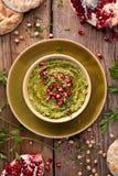 hummus Ziołowy hummus z dodatkiem granatowów ziaren, pietruszki, oliwa z oliwek i aromatycznych pikantność w ceramicznym garnku n obrazy stock