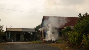 Humo de la hierba ardiente delante de la casa del vintage - Vietnam rural fotografía de archivo libre de regalías