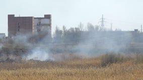Humo del fuego delante de edificios de la fábrica almacen de metraje de vídeo