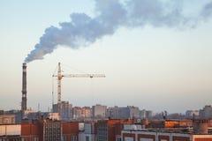 Humo del tubo de la caldera sobre los tejados de edificios altos de apartamentos Foto de archivo