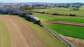 Humo que sopla del tren de pasajeros del vapor a lo largo del campo de Amish según lo visto por un abejón almacen de metraje de vídeo